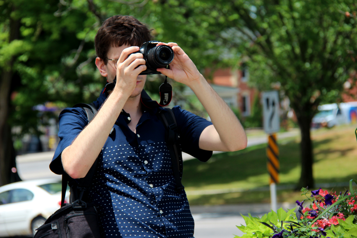 Michal takes a photo with a DSLR camera while standing near a road.