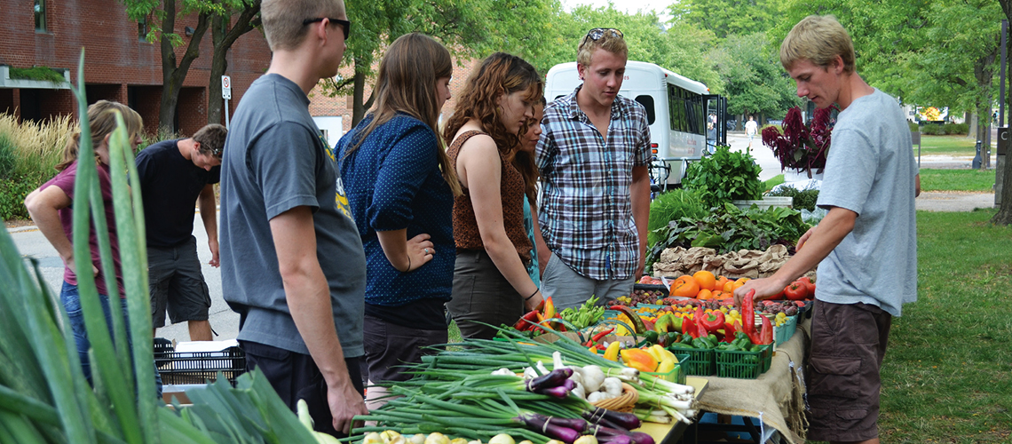 People buying vegetables at a stand.