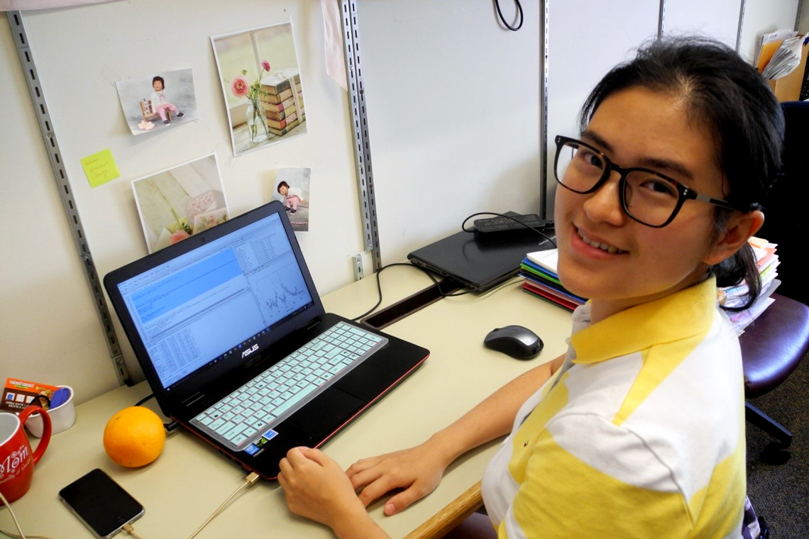 Qin sits at desk working on laptop.