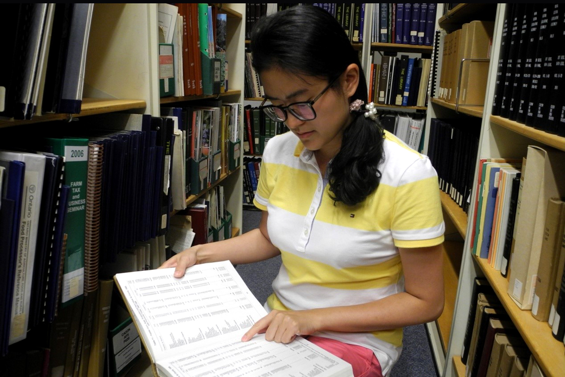 Qin crouches in between two library stacks, looking at a book.