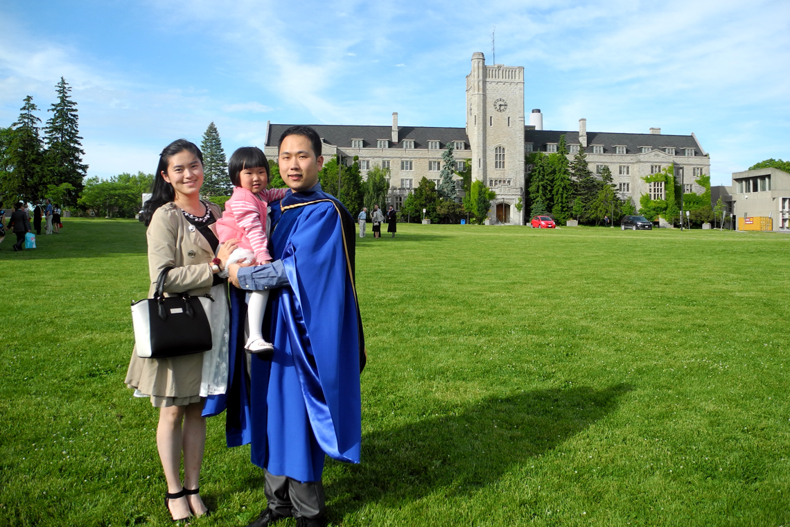 Qin stands with daughter and husband on Johnston Green at husband's graduation.