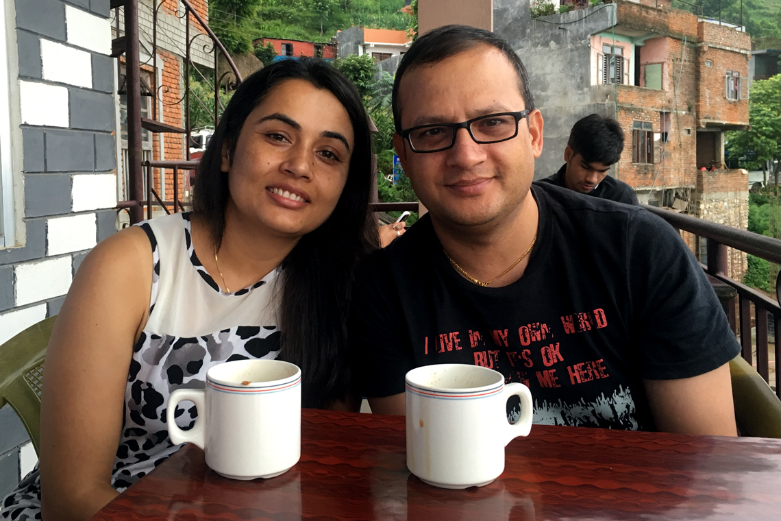Rachana and husband sit at outside table with coffee mugs.
