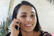 Rachana Devkota smiles while on the phone.
