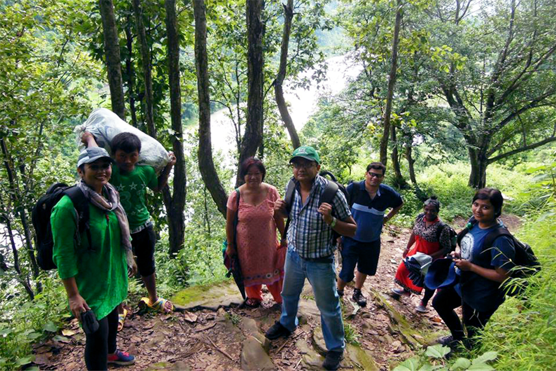 Rachana stands with a group of coworkers on a hill in a forest.