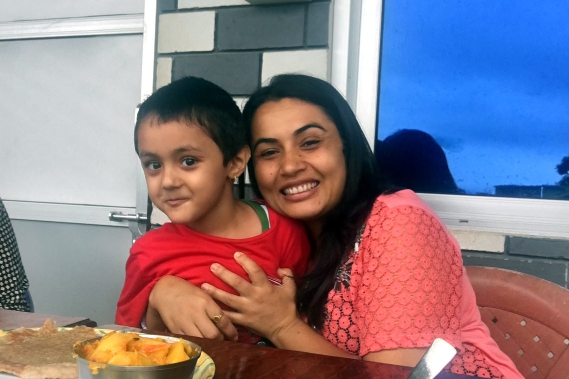 Rachana hugs her son at breakfast table.