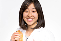 Head shot of Stephanie in a lab coat holding a loaf of bread.