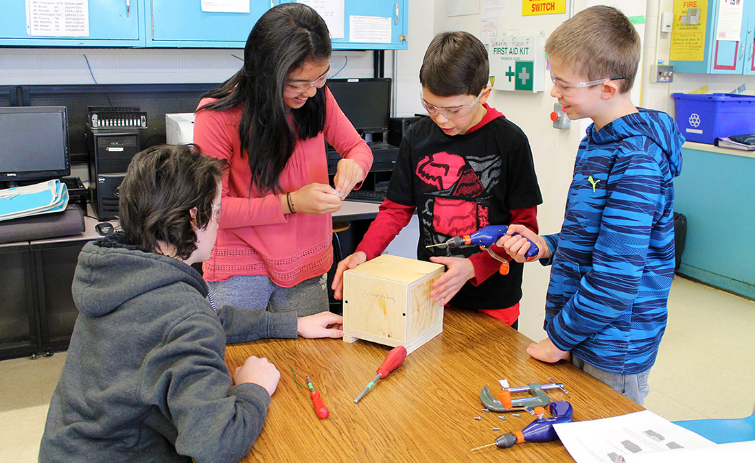 Four students build bumble bee nest boxes in a classroom.