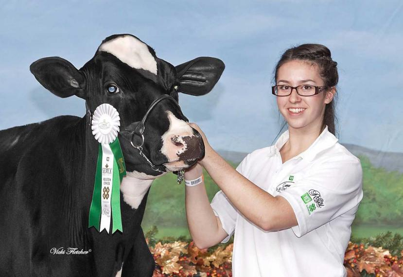 Emma poses while holding her prize winning cow