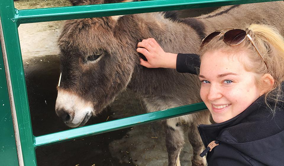 Natalia poses with a donkey.