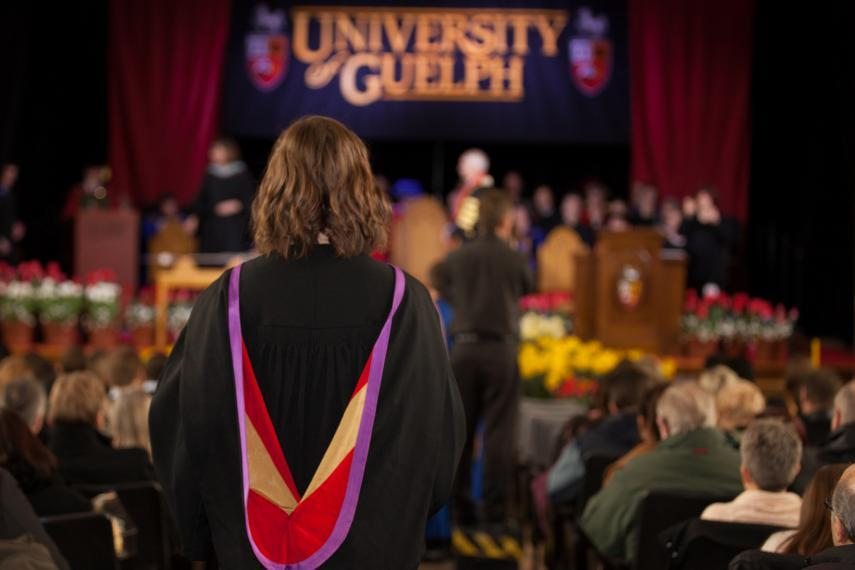 A student in her graduation gown walks up to the stage to receive her degree.