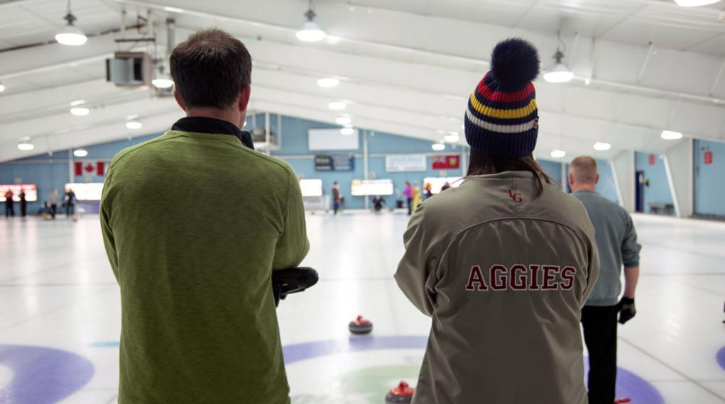 Male and female Aggies look out at curling ice
