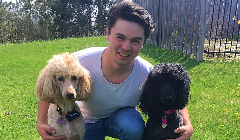 Thomas kneels and smiles with two dogs.