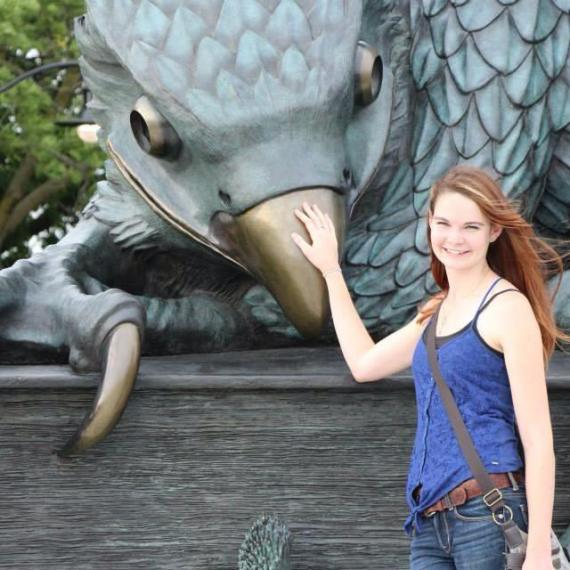 Glenna stands with hand on beak of large Gryhon statue