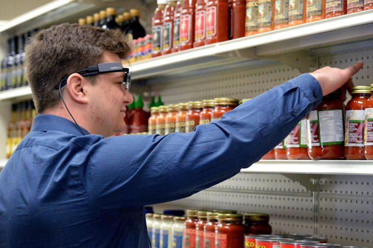 Male student reaches for pasta sauce jar while wearing eye-tracking glasses
