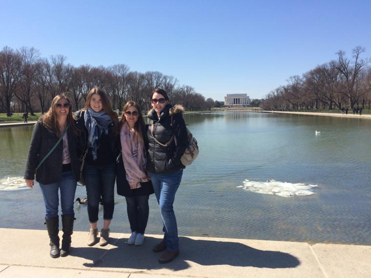 Four female students stand in front of the large pond in front of the Masters students in front of the Lincoln Memorial at the National Mall