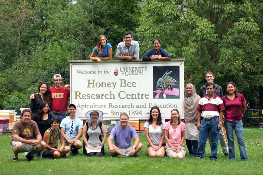 Group of students and faculty stand with large Honey Bee Research Centre sign