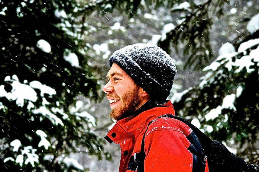 Kevin in snowy evergreen forest wearing toque and red jacket