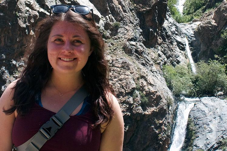 Laura Stortz stands in front of a rocky cliff with a small waterfall flowing through it.