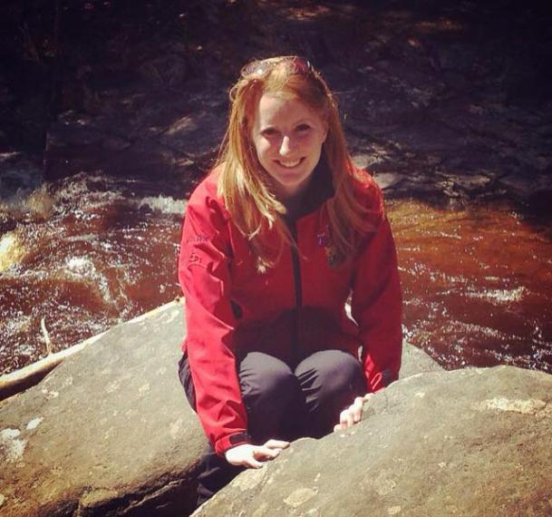 Marnie wearing red jacket and crouching by rocks and a stream of water