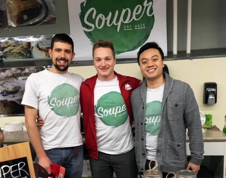 "Brandon, Dylan and Allan stand together wearing matching ""Souper"" shirts and ""Souper"" sign in background"