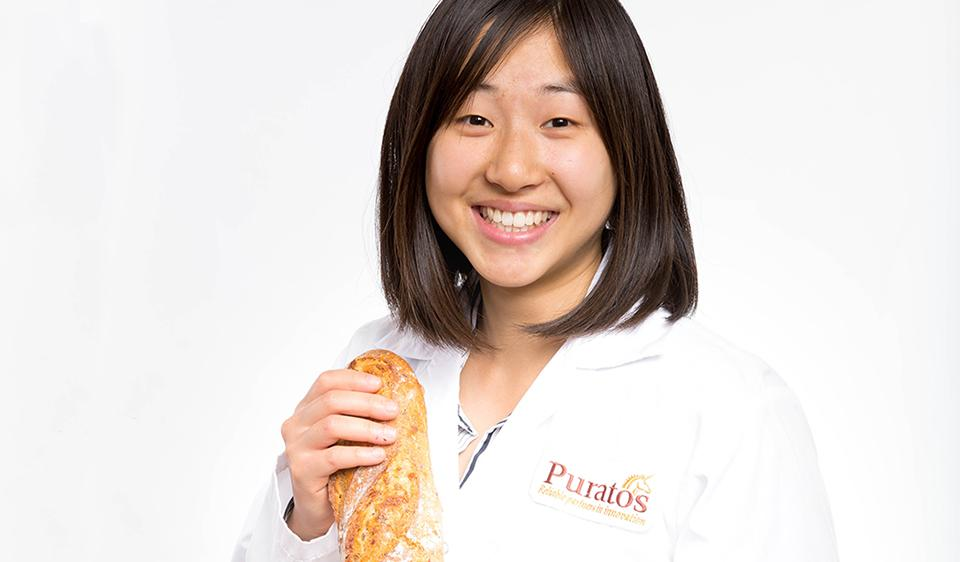 Head shot of Stephanie in a lab coat, holding bread.
