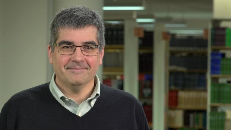 John Cranfield smiles, bookshelves behind him