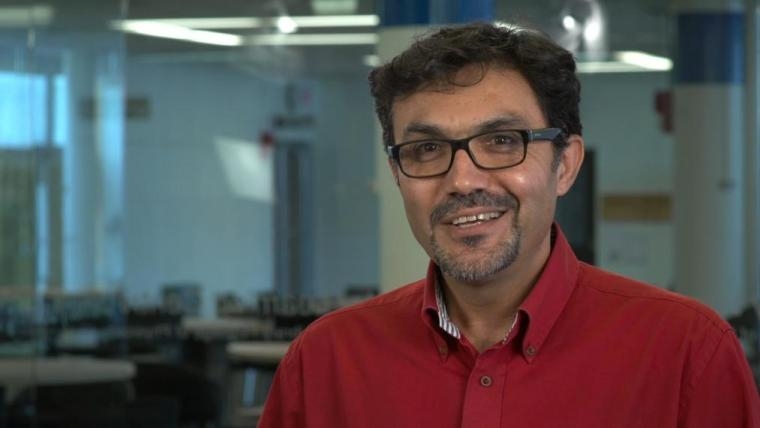 Ali Navabi in red shirt smiling in front of glass walled classroom