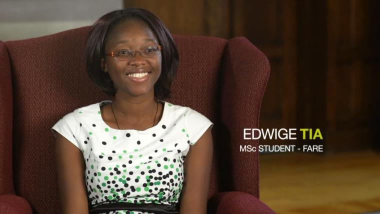 Edwige Tia smiling in a large arm chair, her name written out in overlay text