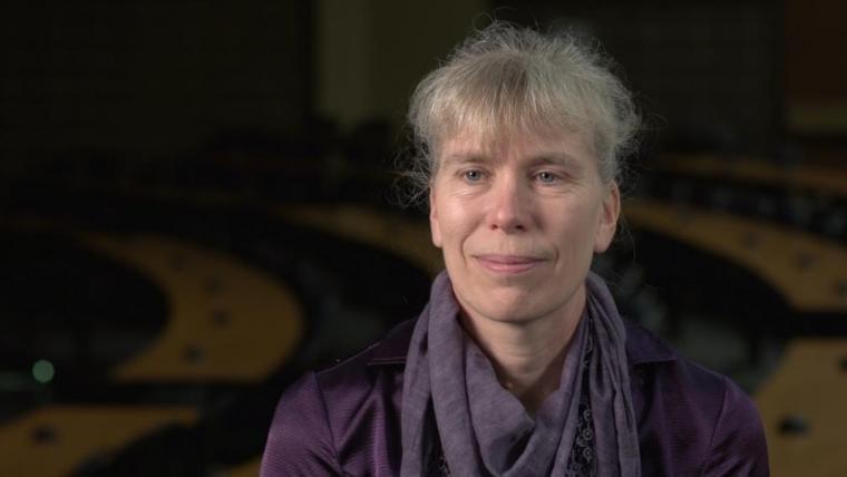 Prof. Katrina Merkies head shot sitting in dark lecture hall