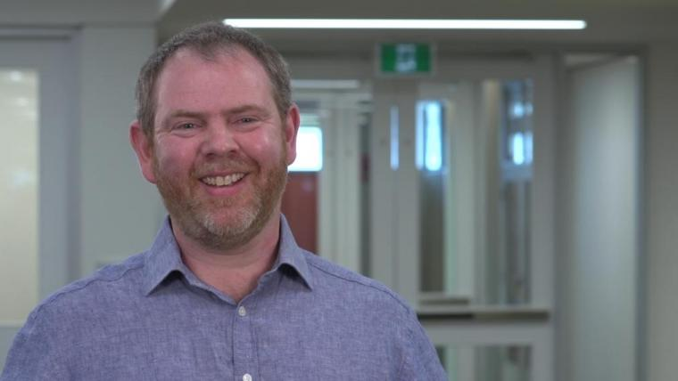 Nigel Raine smiling in front of glass doors