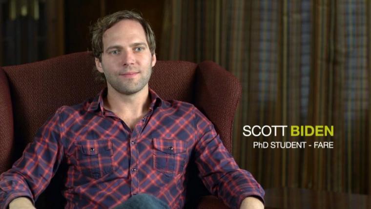 """Scott sitting in arm chair with """"Scott Biden PhD FARE"""" text overlay"""