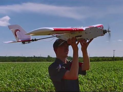 Student in field holds white and red drone plane