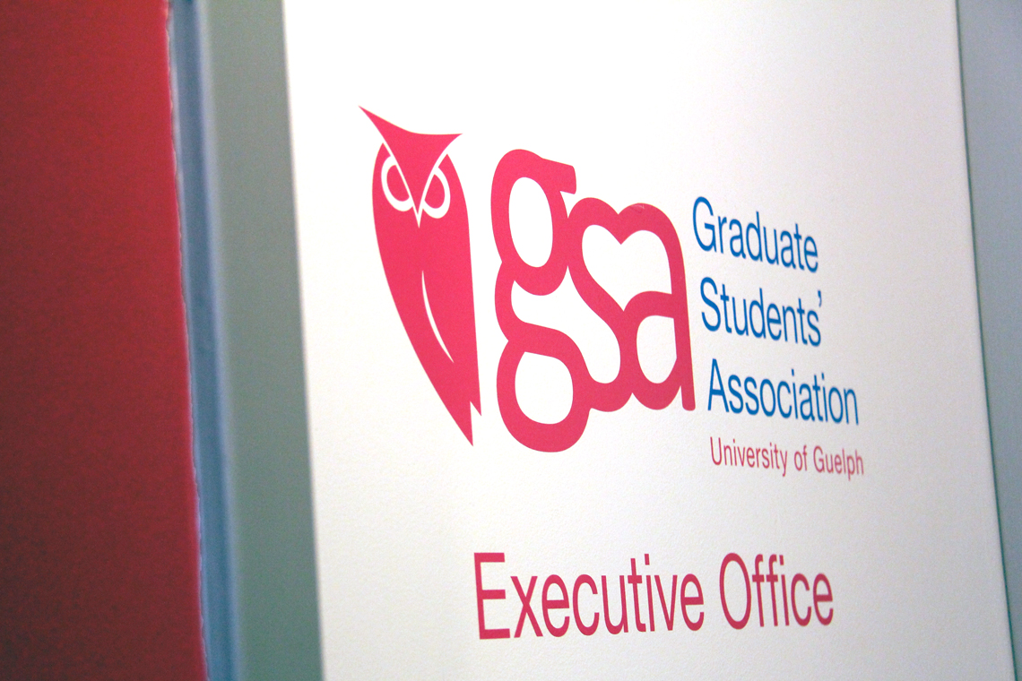 Graduate Student Association logo on a white door.