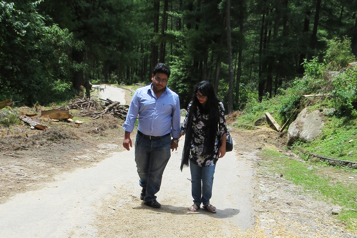 Syer walks with wife on a pathway through the forest.