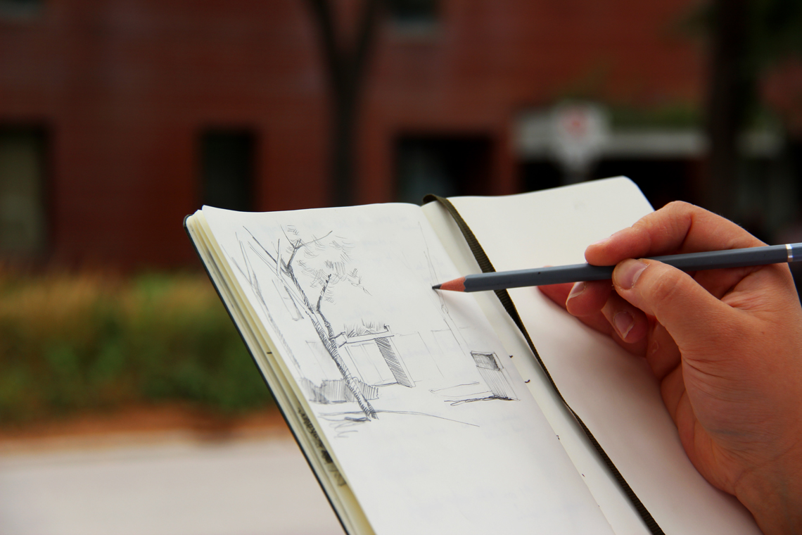 Close up of a hand sketching a building in a small notebook.