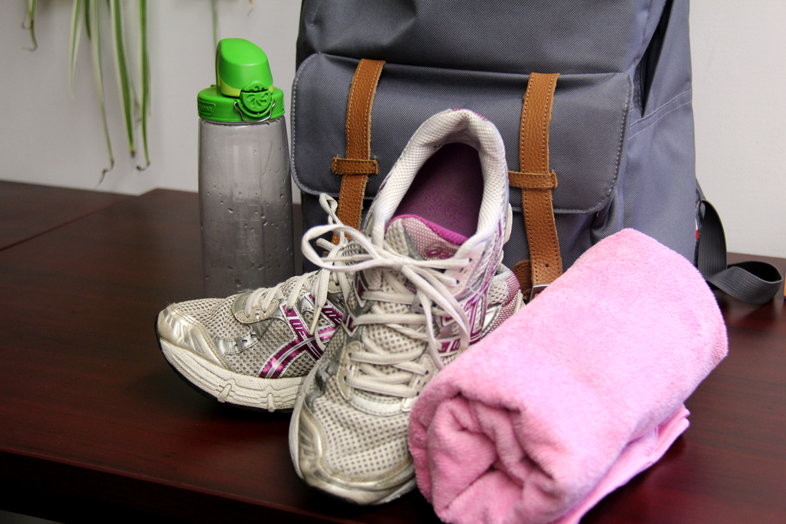 A backpack, water bottle and pair of running shoes on a desk.