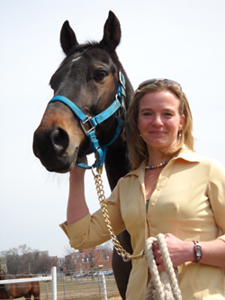 Wendy Pearson standing with brown horse wearing blue halter