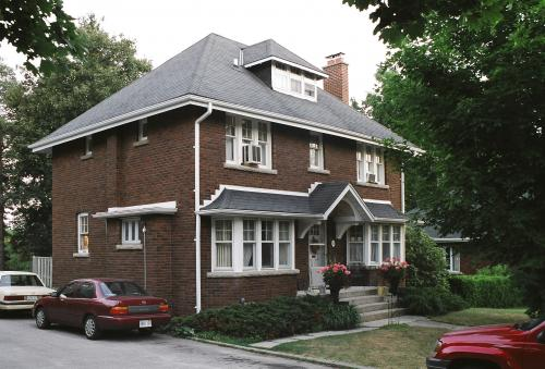 11 University Avenue East is a 1926 brown-brick house with white trim and four steps up to the front door