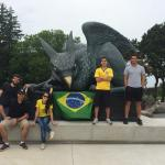 Science without Borders students in front of the Gryphon statue with a Brazil flag.