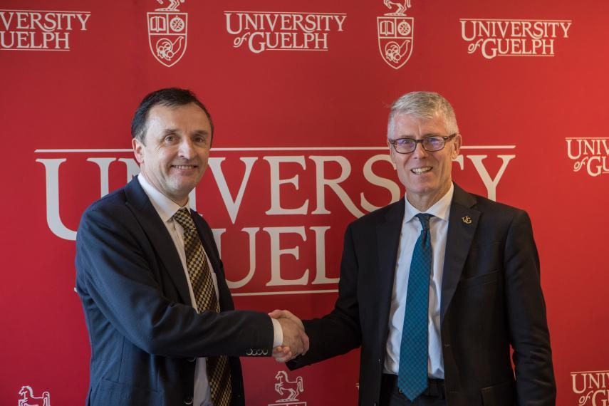 John Brennan and Malcolm Campbell shake hands in front of a UofG backdrop