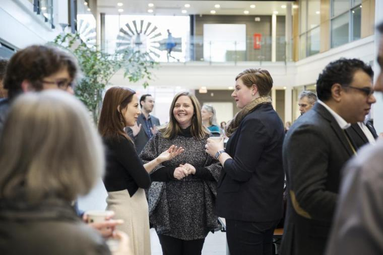 Professionals talking in networking-style setup in a brightly lit atrium
