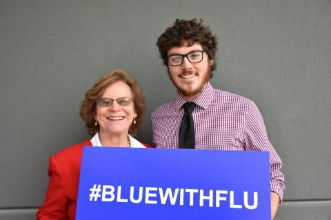 Photo of Cate Dewey and Adam Beswick holding a #bluewithflu sign