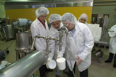 Photo of three people wearing lab coats and head coverings look at ice cream coming out of a faucet
