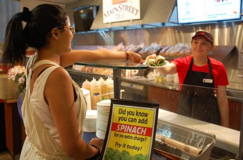 """Hospitality Services' server Kendal West (right) delivers a wrap with added spinach to student Amia Khosla at the University Centre deli sandwich station. A sign beside Amia says """"Did you know you can add spinach for no extra charge? Try it today!"""""""