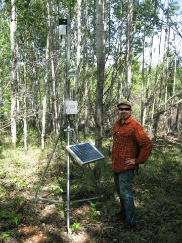 Prof. Gedalof stands in a forest beside a temporary weather station - a solar panel and wiring, mounted on a metal tripod