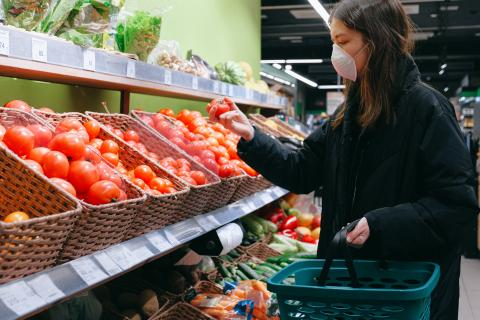 Woman wearing a mask holding a tomato in front of a tomato display