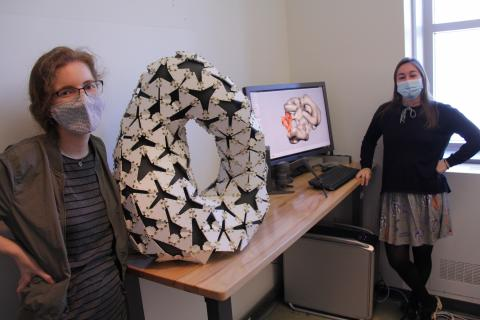 Diana Pfeffer (left), MLA student, stands beside a sculpture on a table. The sculpture is oval and black and white. Also on the table is a computer monitor.  In the right of the photo is Michael Richardson, an MFA history student.