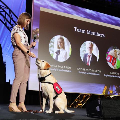 lady standing on the left with service dog sitting at her feet. both appear on a stage