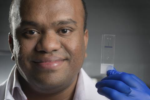 close-up of Suresh Neethirajan holding the lab on a chip