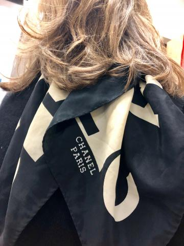 A woman's back is to the camera.  Her hair is brown, and shoulder length.  She wears a black sweater and a black and white scarf that says Chanel, Paris on it.